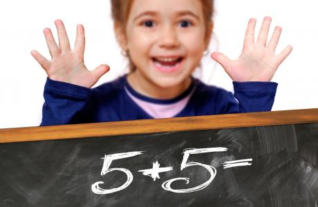 small child smiling with math problem on board