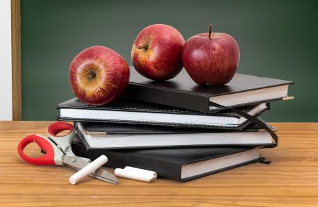 books with apples on top